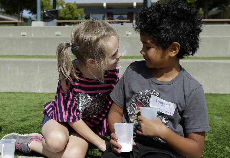 Image: campers Gracie, left, leans toward Nugget during an activity at the Bay Area Rainbow Day Camp in El Cerrito, Calif.
