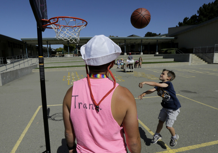 Image: camp instructor Kris Gambardella watches as camper Wilson shoots baskets at the Bay Area Rainbow Day Camp in El Cerrito, Calif.
