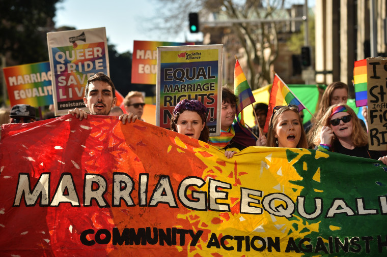 Image: Supporters of same sex marriage carry banners and shout slogans as they march in Sydney on August 6, 2017.