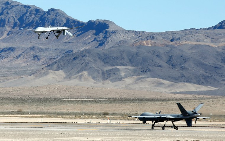Image: An MQ-1B Predator remotely piloted aircraft (RPA) flies past a MQ-9 Reaper RPA as it taxis during a training mission at Creech Air Force Bas