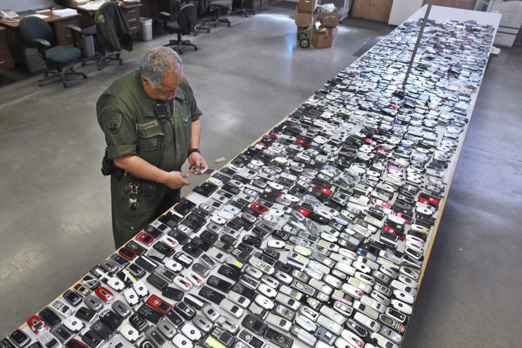 Image: A correctional officer inspects one of the more than 2,000 cell phones confiscated from inmates at California State Prison,
