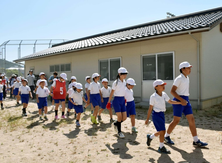 Image: Schoolchildren leave the compound of their school during an evacuation drill