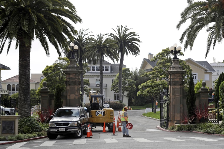 Image: A construction workers stands in front of a gate leading into the Presidio Terrace neighborhood