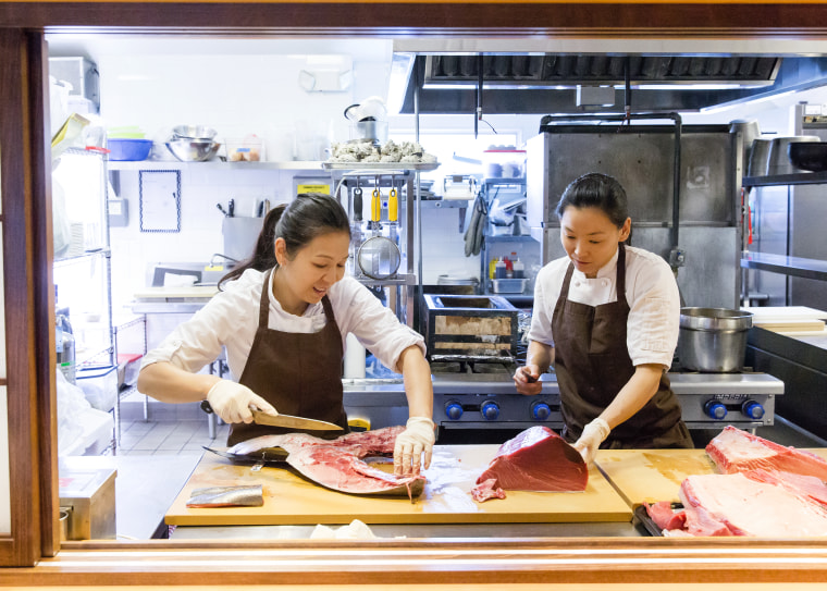 Chef Niki Nakayama (left) slices fish with sous chef and wife Carole Iida-Nakayama. At her Los Angeles restaurant, Nakayama specializes in a type of multi-course dining known as kaiseki.