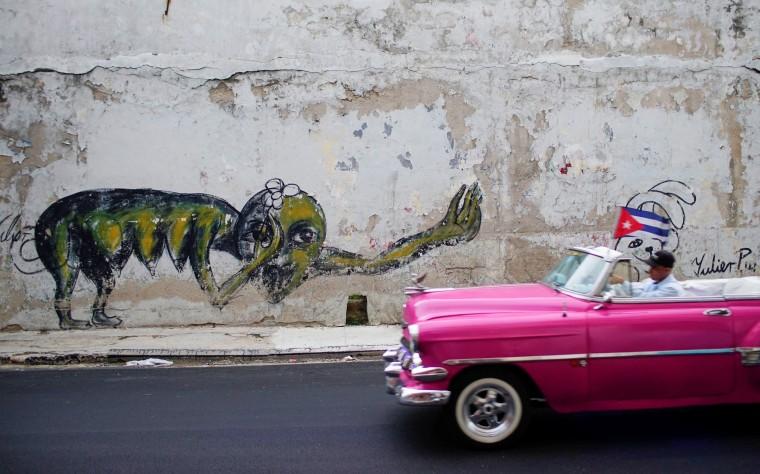 Image: A vintage car passes by a graffiti of Cuban Artist Yulier Rodriguez in Havana, Cuba
