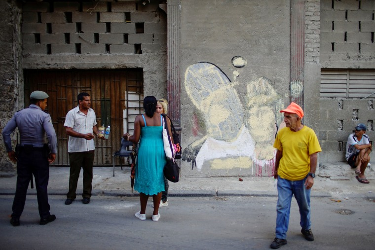 Image: A man escorted by a police officer paints over a graffiti of Cuban artist Fabian Lopez