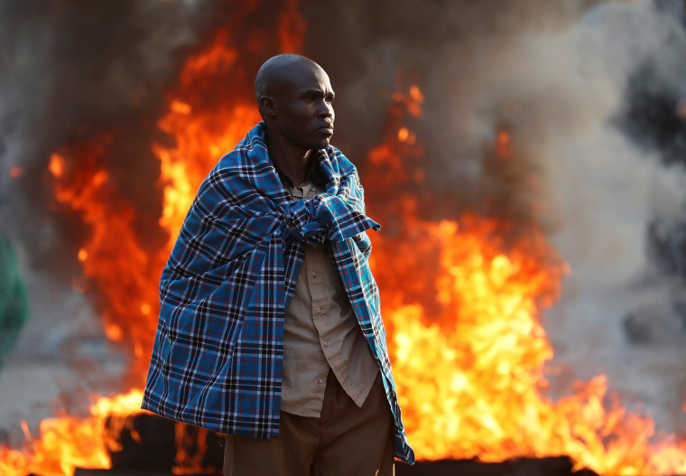 Image: A supporter of opposition leader Raila Odinga stands in front of a burning barricade in Kibera slum in Nairobi