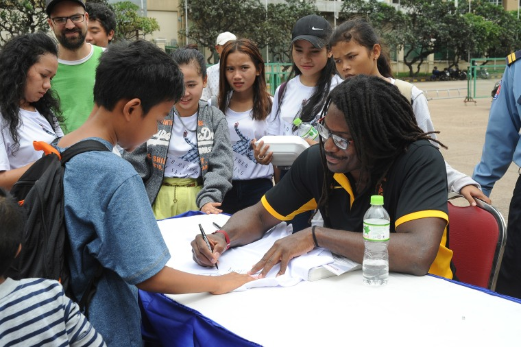 Neftalie Williams signing autographs in Cambodia.