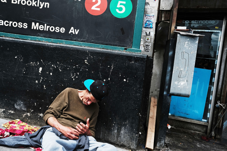 Image: A man rests against a wall appearing to be under the influence of drugs on a street in the South Bronx