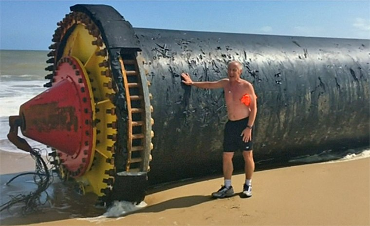 A man poses with a giant pipe that washed up on a beach in Norfolk, England.
