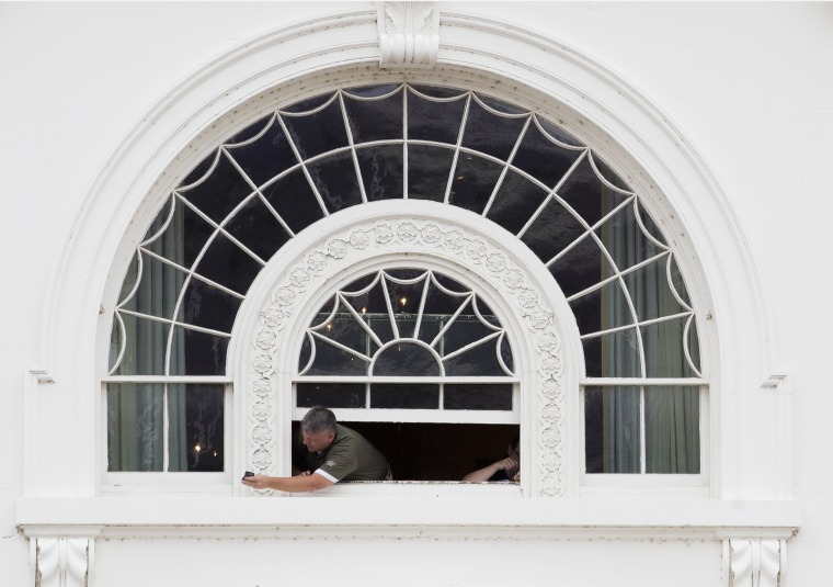 Image: A worker reaches out of a window of the White House