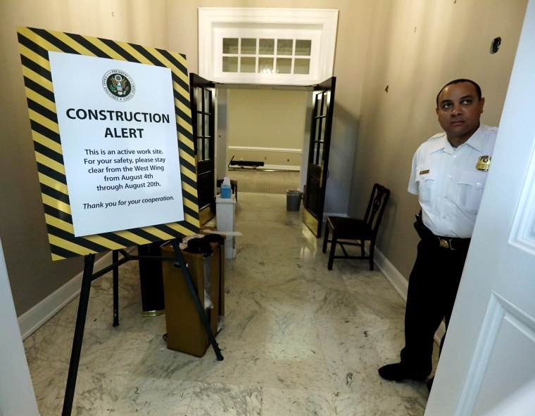 Image: A uniformed U.S. Secret Service officer stands guard at the closed main entrance to the West Wing
