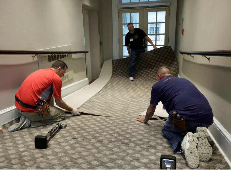 Image: Construction workers lay carpet on a ramp