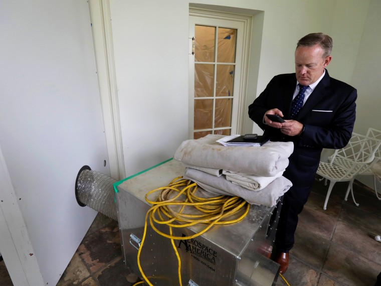 Image: Spicer checks his email outside the empty Oval Office during renovations at the White House in Washington