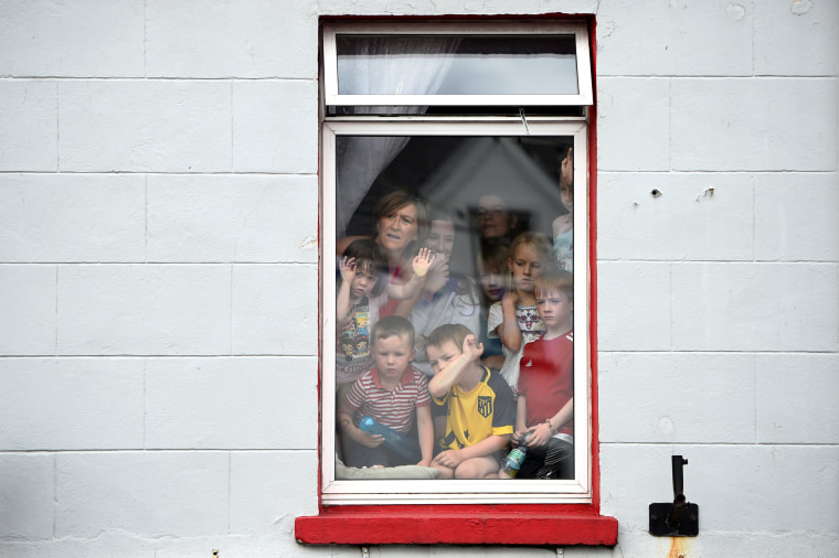 Image: People crowd into a window to see a wild goat paraded through the town before being crowned King Puck for three days in Killorglin
