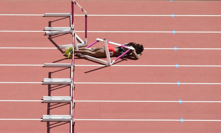 Image: Deborah John lies on the track after falling in the women's 100m hurdles athletics event