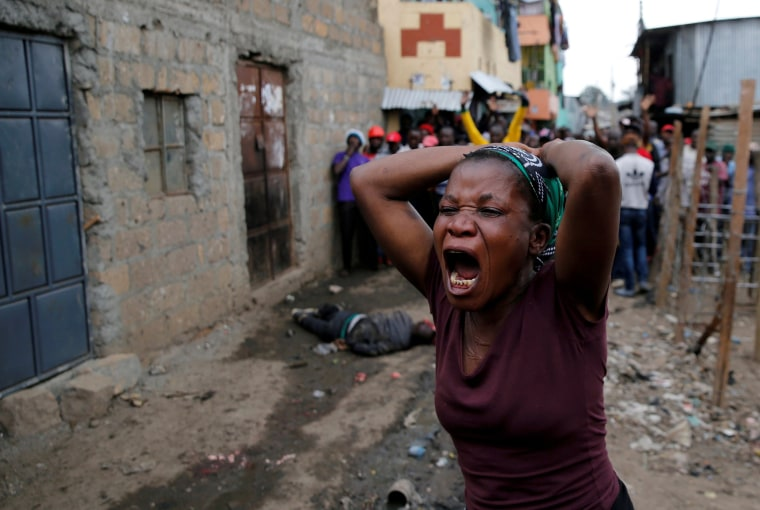 Image: A woman gestures as she mourns the death of a protester in Mathare, in Nairobi