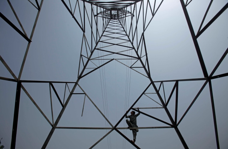 Image: A worker of PESCO climbs up a high-voltage pylon in Peshawar