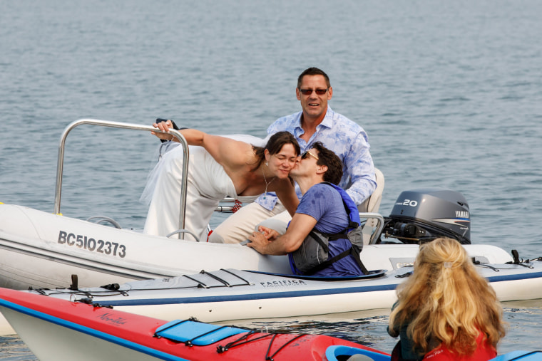 Image: Newlyweds Michelle and Heiner Gruetzner approach Canada's Prime Minister Justin Trudeau while he was kayaking off Sidney