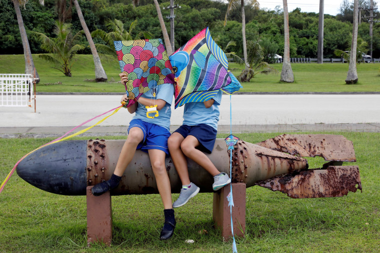 Image: Pupils sit on the World War II remnants of a torpedo at Asan Memorial Park on the island of Guam