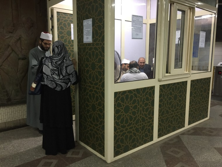 Image: Sheikhs provide theological advice to passengers at the temporary kiosk at Shouhada' subway station in Cairo.