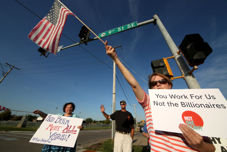 Image: Deb Rasmussen of Independence, Iowa, foreground protests with Laura Wright and Jacob Krapfl outside an Iowa Tea Party event for U.S. Rep. Rod Blum in Dyersville, Iowa, Aug. 10, 2017.