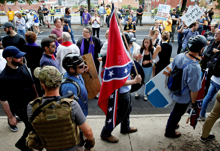 Image: A white supremacists carries the Confederate flag as he walks past counter demonstrators in Charlottesville Virginia