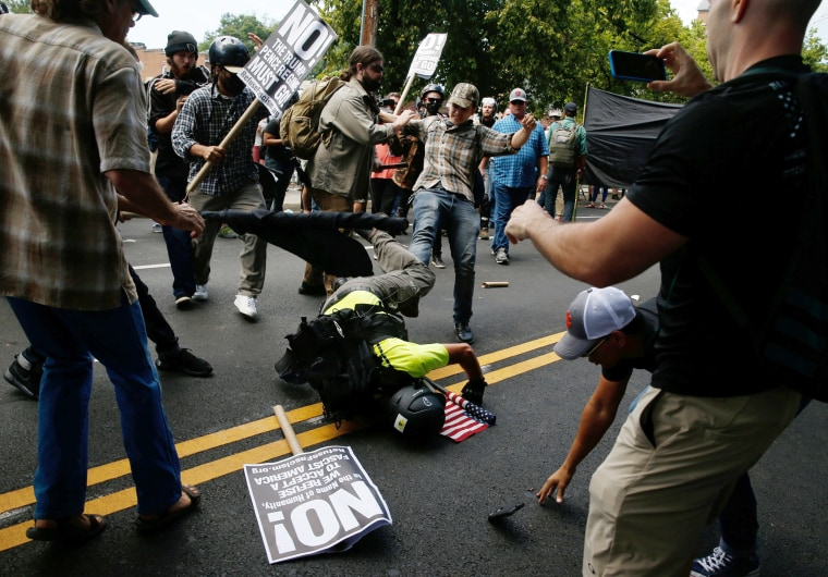 Image: A man hits the pavement during a clash between members of white nationalist protesters against a group of counter-protesters in Charlottesville