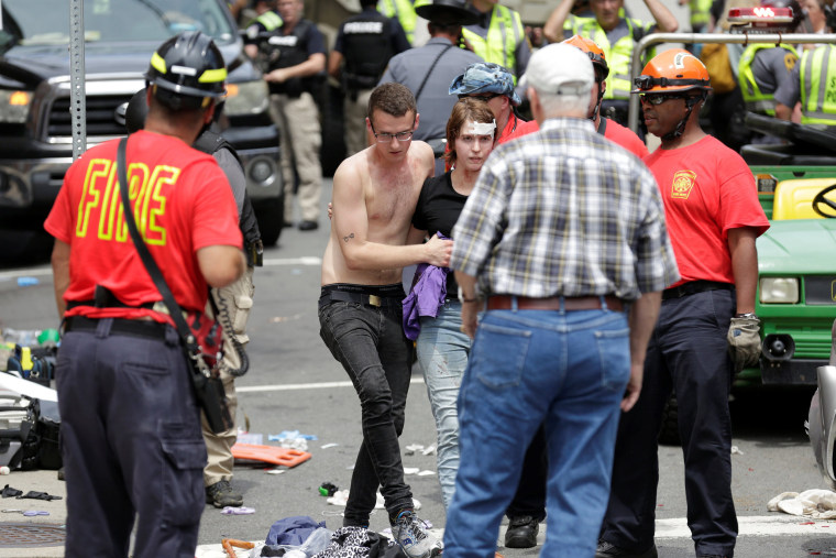 """Image: A woman who was injured when a car drove through a group of counter protestors at the \""""Unite the Right\"""" rally is helped in Charlottesville"""