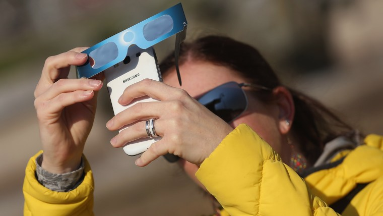 A woman uses special glasses and a smartphone to photograph eclipse