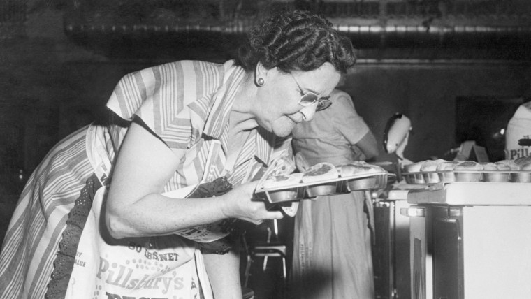 A participant pulls her 80 minute bicuits fresh out the oven during the 1949 bake-off.