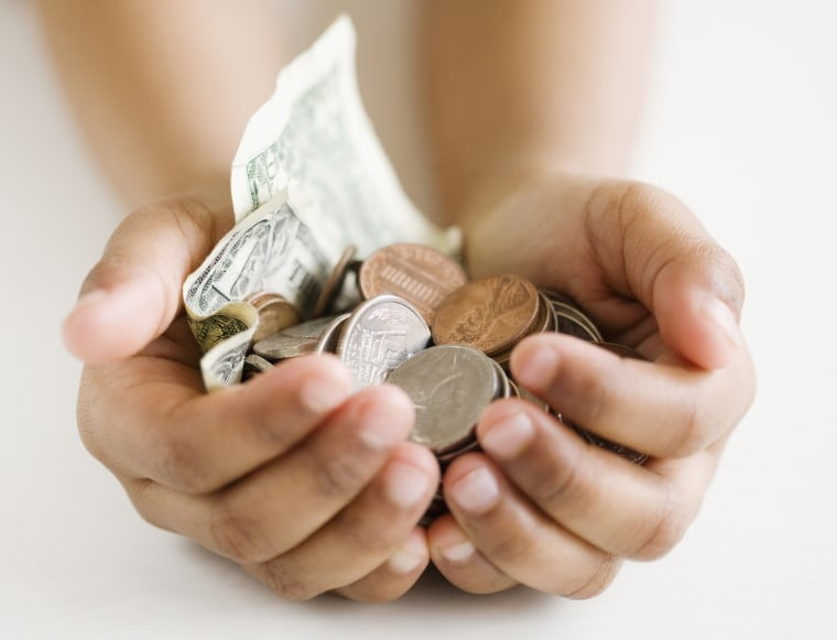 Image: A child holds money in her hands