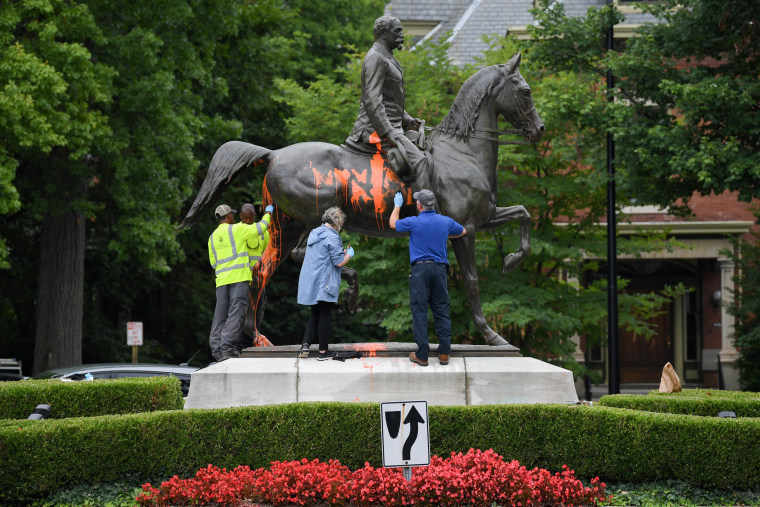 Image: Municipal workers attempt to remove paint from a monument dedicated to Confederate soldier John B. Castleman that was vandalized late Saturday night in Louisville
