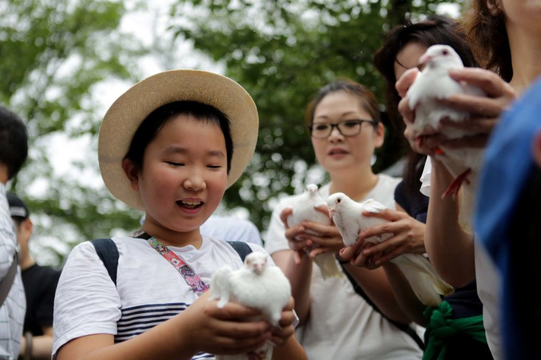 Image: Attendees hold doves, the symbol of peace