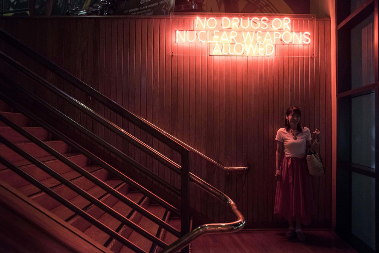 "Image: A woman poses for a friend under a sign reading ""No drugs or nuclear weapons allowed"""