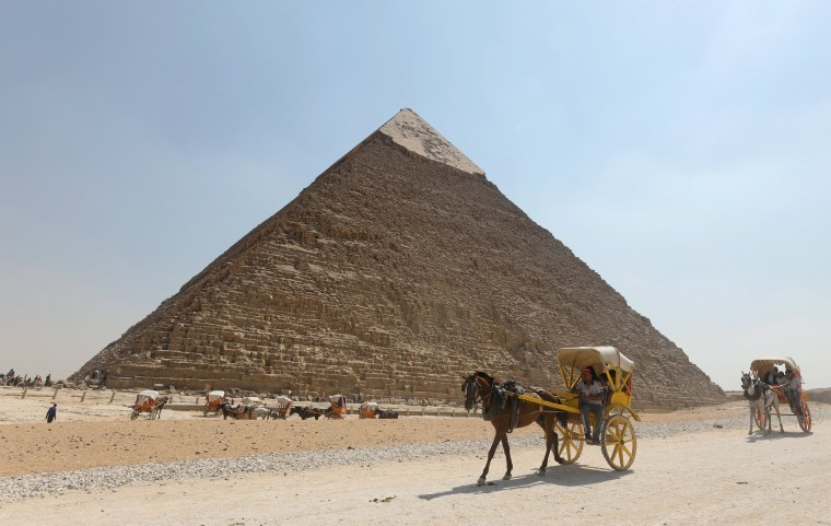Image: Tourists ride in horse carts in the Giza pyramids area, on the outskirts of Cairo