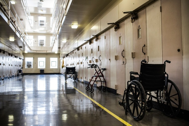 Image: Wheel chairs and walkers sit outside prison cells at California Medical Facility