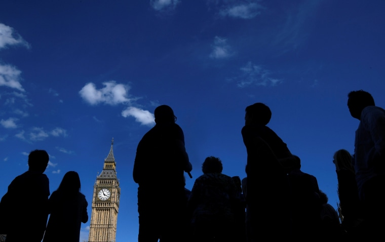 Image: Tourists view the Elizabeth Tower, which houses the Great Clock and the 'Big Ben' bell, at the Houses of Parliament, in central London