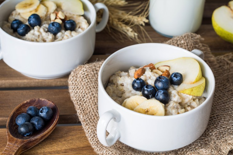 Image: Two bowls of oatmeal with pear, blueberries, almonds and honey