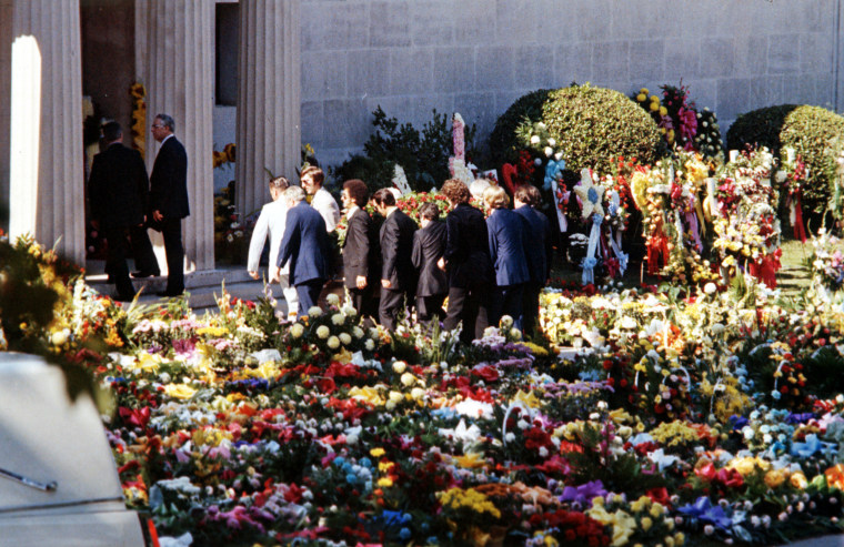 Pallbearers carry the flower-covered coffin ointo the Forest Hills Cemeteries mausoleum.