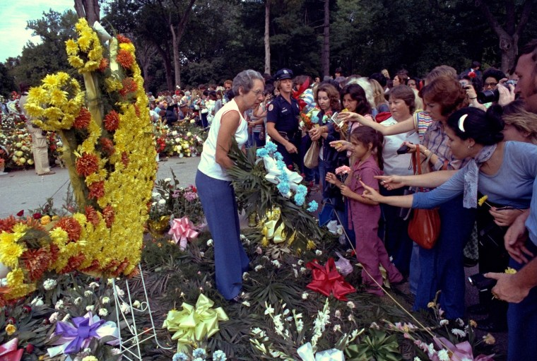 Fans reach out to touch floral arrangements at Forest Hills Cemetery.