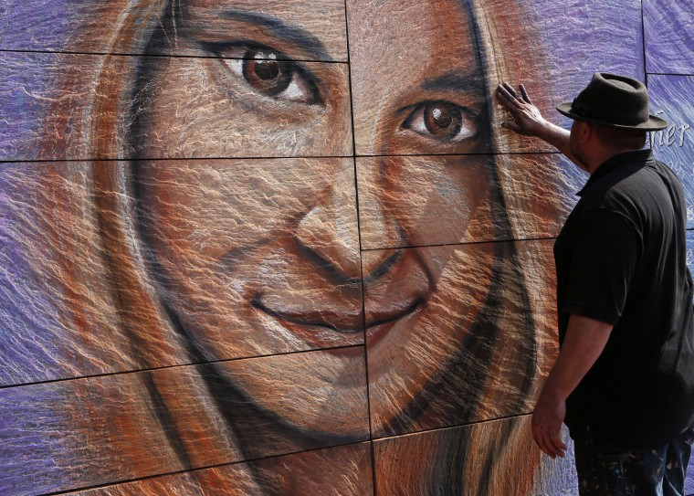 Image: Artist Sam Welty creates a chalk mural of Heather Heyer during her memorial service