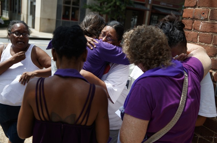 Image: People gather near a memorial for Heather Heyer