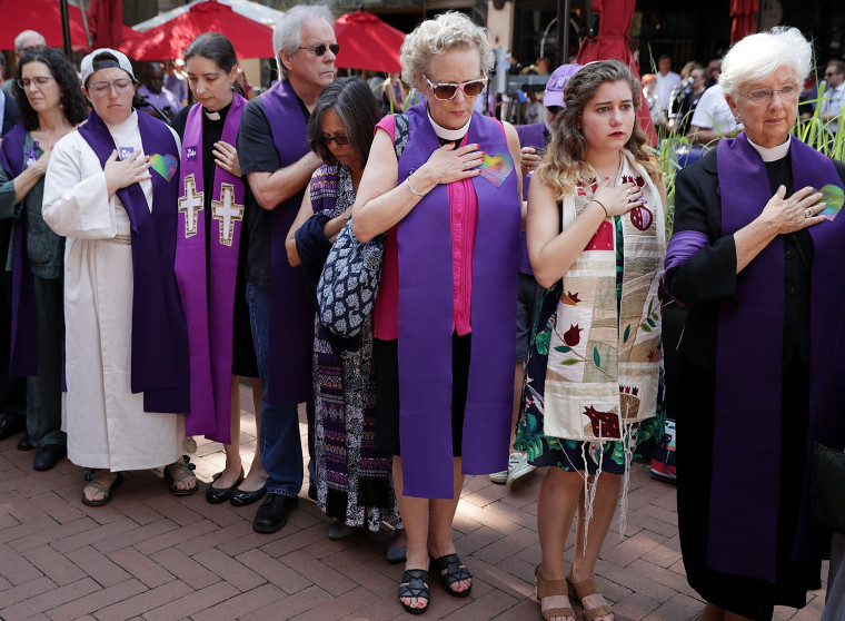 Image: Clergy observe a moment of silence during the memorial service for Heather Heyer outside the Paramount Theater