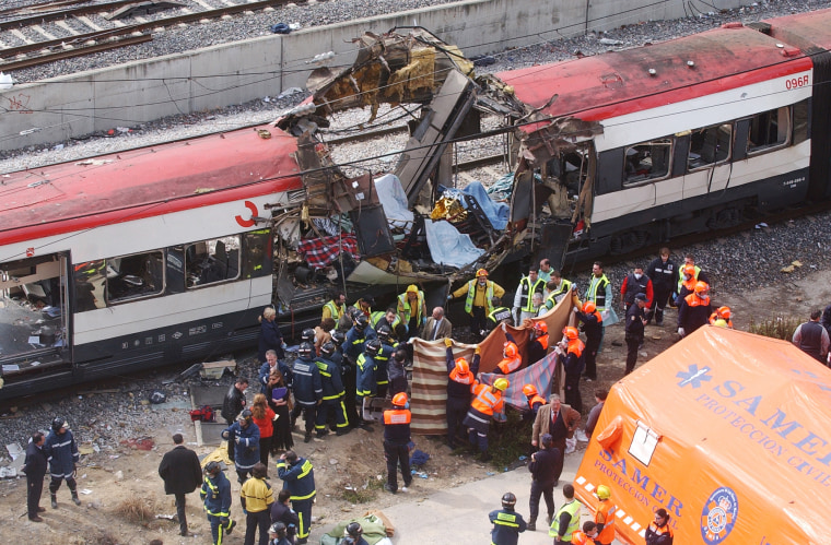 Image: Rescue workers cover up bodies alongside a bomb-damaged passenger train