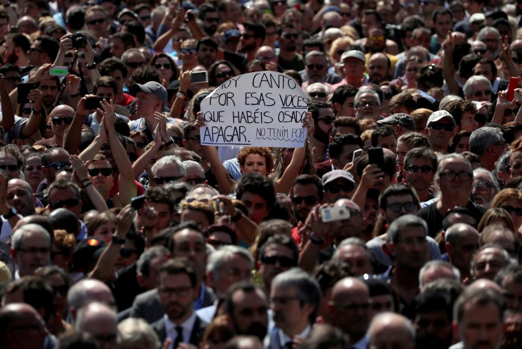 "Image: A woman holds a sign that reads ""I sing today for those voices that you have dared to shut up. We are not afraid"" while observing a minute of silence at Placa de Catalunya, a day after a van crashed into pedestrians at Las Ramblas in Barcelona"