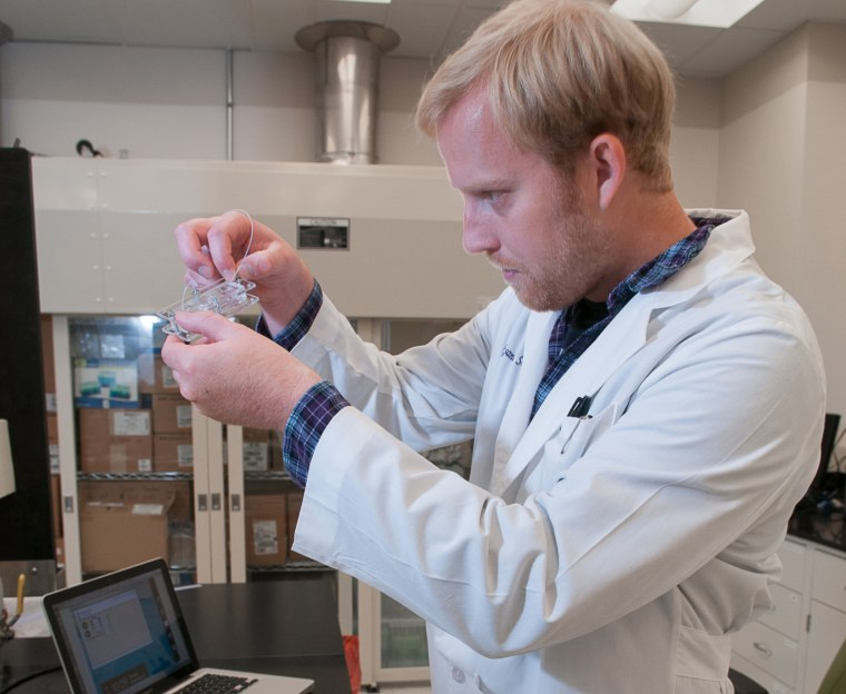 """Dr. Aleksander Skardl demonstrates a """"body-on-a-chip,"""" a method of testing cell reaction to toxins, in a lab at Wake Forest Institute for Regenerative Medicine."""