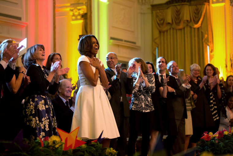 First lady Michelle Obama show her appreciation during the White House Talent Show in 2014 hosted by the President's Committee on the Arts and the Humanities.