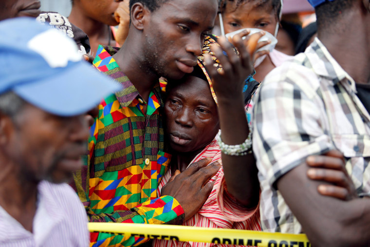 Image: A mother who lost her son during the mudslide gets consoled by a sympathiser near the entrance of Connaught Hospital in Freetown