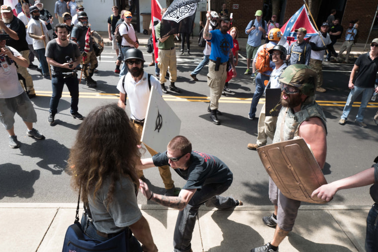 Image: A neo-Nazi man rips a sign out of a protester's hand and snaps it in half on his knee before throwing it on the floor and walking off.